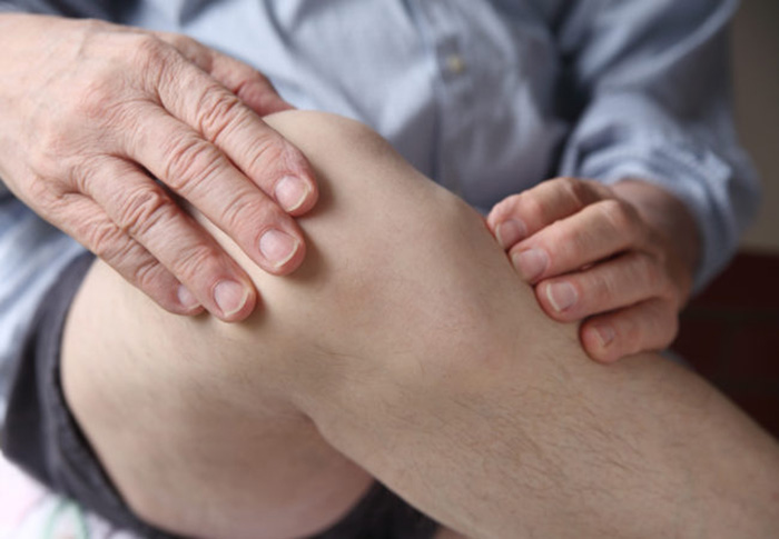 a man with his hands on a painful knee joint