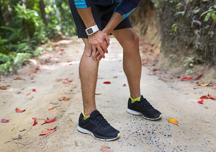 Runner holding sore leg, knee pain from running or exercising, j