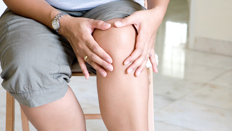 Woman tenderly massaging her painful knee